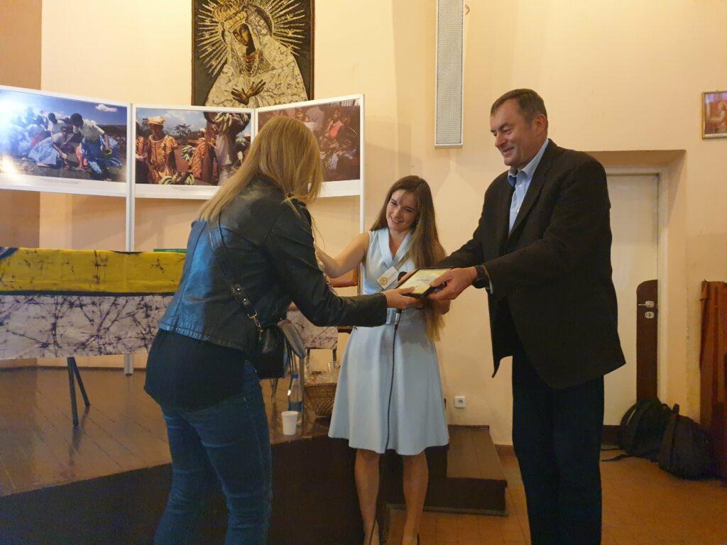 Koordynator Adopcji Serca oraz koordynatorka wolontariatu Sara Kulesza wręczają okolicznościowy certyfikat wolontariuszce programu